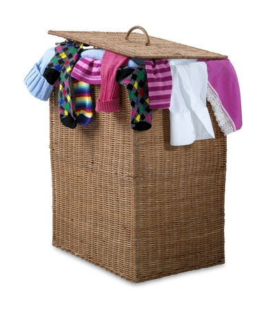 overflowing: an overflowing wicker laundry basket isolated on white with clipping pathshowing a bust hectic lifestyle