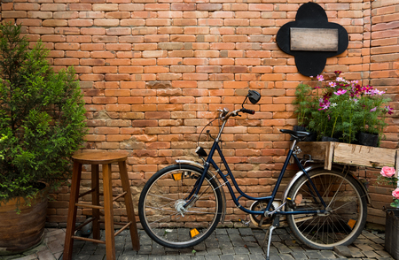 Blue bicycle with wooden box of flowers on brick wall background. Stock Photo