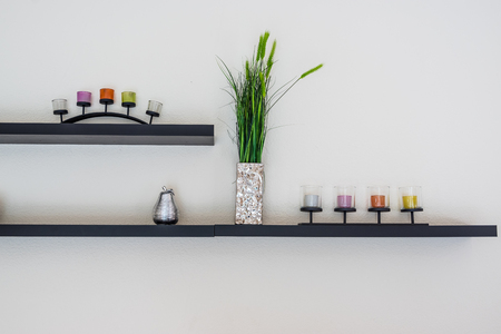 Decorative candle with flower vase on wooden shelf. Stok Fotoğraf