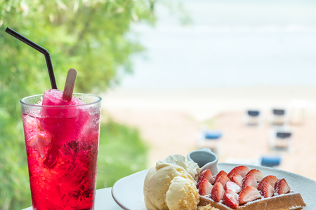 Srawberry waffle with vanilla ice cream and red drink with ice cream on blurred beach background Stock Photo