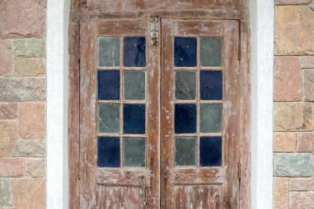 Vintage architecture wooden door decorated with colorful stained glass and stone bricks wall Stock Photo
