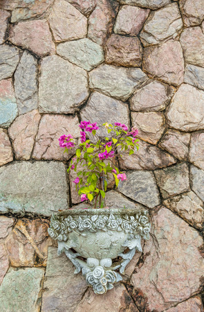 Decoration stone wall with pink flower in roman pot. Gardening vertical fence in antique architecture. Stockfoto - 122774222
