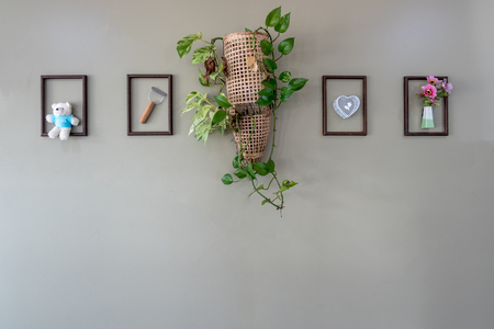 Decorated gray wall with cute stuffs in wooden frame picture and flower bouquet