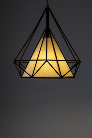 Modern lamp hanging down from ceiling in the dark background. Minimalist chandelier with glowing warm light from bulb. - Image 版權商用圖片