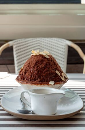 Chocolate brownie bingsu or Korean shaved ice cocoa topping with sliced almond