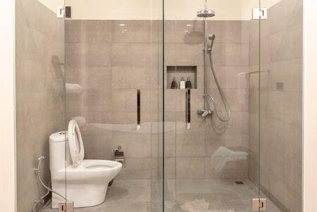 Interior de baño moderno con mampara de vidrio transparente. Ducha y wc en estilo contemporáneo.