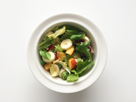 A bowl of fresh healthy fruit and vegetable salad with mixed leaves, nectarine and banana on a white table.