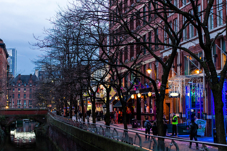 MANCHESTER, UNITED KINGDOM - 5 March, 2016: Evening view of a lit up street and canal in the city of Manchester in the north of England.
