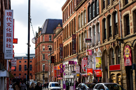 MANCHESTER, UNITED KINGDOM - 5 March, 2016: A busy street with Chinese restaurants and stores in the Chinatown part of Manchester.