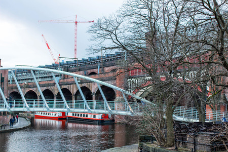 MANCHESTER, UNITED KINGDOM - 5 March, 2016: A view of river canal in the city of Manchester with bridges, boats and tower cranes in the background.