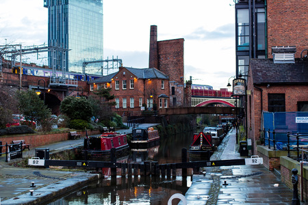 MANCHESTER, UNITED KINGDOM - 5 March, 2016: An evening view of a river canal in Manchester with boats, bridges and a passing train.
