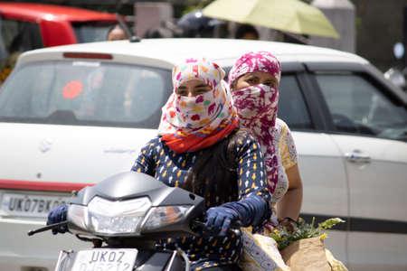 Dehradun, Uttarakhand/India - September 06 2020:Women going on a scooter covering their face. Editoriali