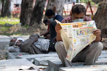 Dehradun, uttarakhand/India - August 14 2020:A men reading newspaper, wearing face mask.