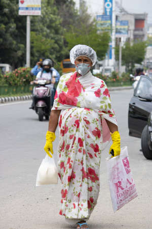Dehradun, Uttarakhand/India - September 08 2020: A woman carrying household items wearing face mask and head cover.