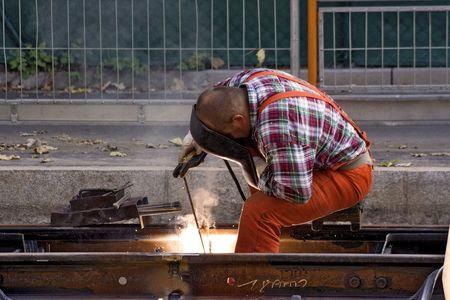steelwork: Construction Worker Fixing Rails (Horizontal View)