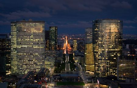 parisian scene: Night shot from Arc de la Defense over the city of Paris. Lit skyscrapers and Champs Elysee in the background. Stock Photo