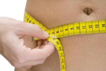 decreasing in size: Donna misurare la sua vita. Sfondo bianco.  Archivio Fotografico