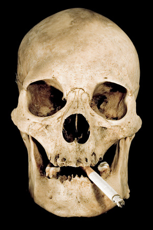 Human skull with cigarette isolated on a black background.