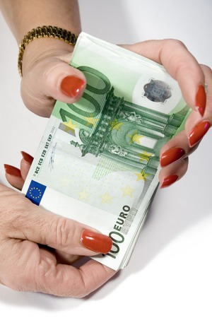 moneyed: Female hands holding a bunch of banknotes.