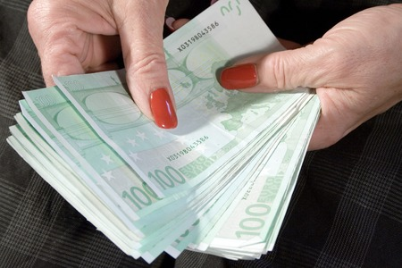 Detail shot of an elder businesswoman with a bunch of banknotes