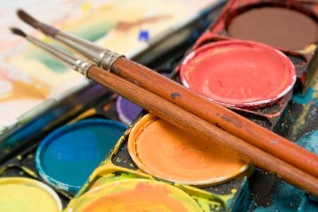 Détail tiré sur une boîte d'aquarelles et deux pinceaux.