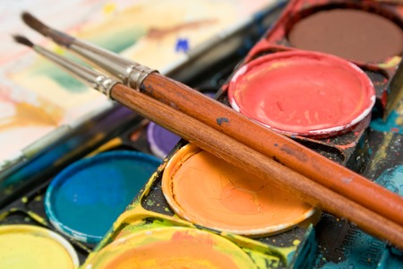 art and craft equipment: Detalle tirado en una caja de watercolors y de dos brochas.