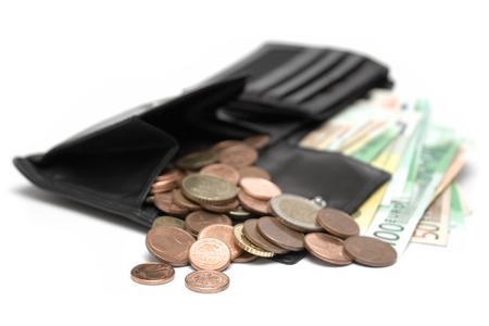 Black leather purse full of coins and banknotes. Isolated on a white background.