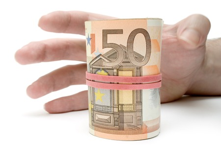 pick money: El acaparamiento de la mano un rollo de billetes de euros. Aislada en un fondo blanco.  Foto de archivo