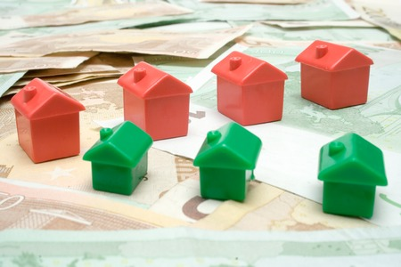 syndicate: Red and green plastic houses standing on Euro bills.