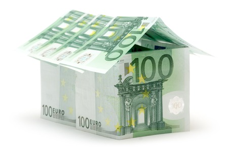 Big house built of several one hundred euro bills. Isolated on a white background. photo