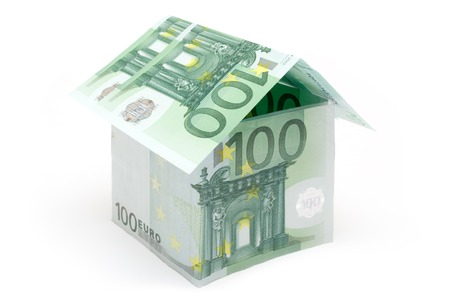 housebuilding: Small house built of several one hundred euro bills. Isolated on a white background.