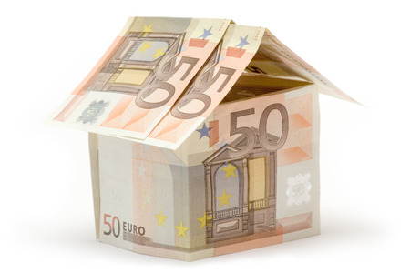 dwell: Small cottage build of fifty euro bills. Isolated on a white background. Stock Photo