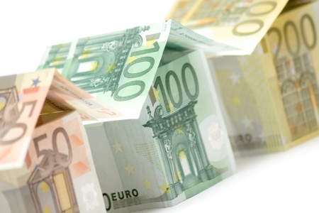 Close view on three colorful houses built of different euro bills. White background. photo