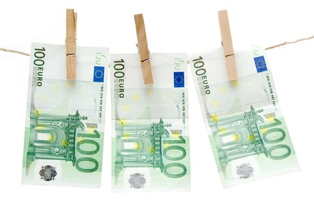 Three one hundred euro bills hanging on a clothesline. Isolated on a white background. photo