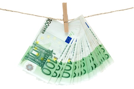 Several one hundred euro bills held by a clothesline. Isolated on a white background. photo