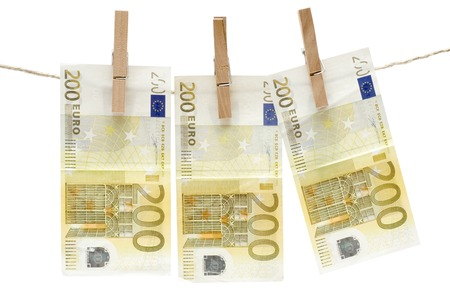 Three two hundred euro bills hanging on a clothesline. Isolated on a white background. photo