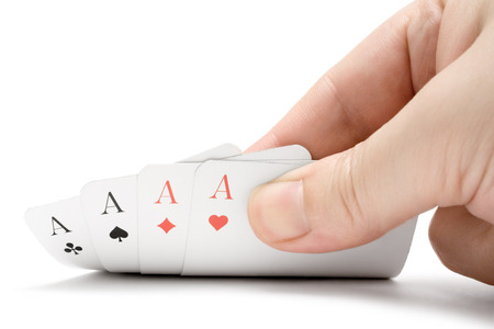 Fingers holding four aces. Isolated on a white background. photo