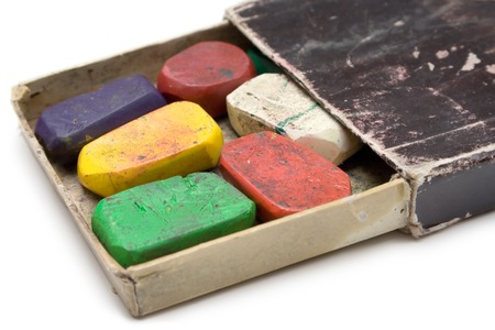 Colorful wax crayons in an old box. Isolated on a white background. photo