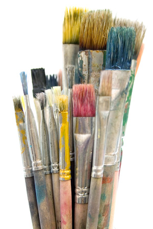 Bunch of dirty paintbrushes in a glass. Isolated on a white background. photo