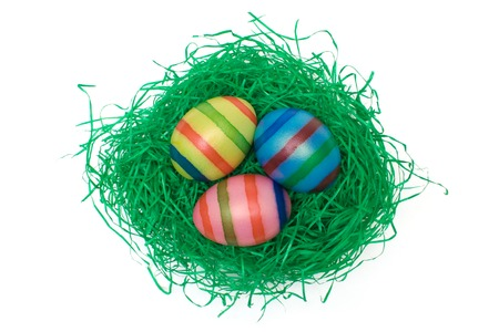 Colored eggs on artificial grass. Isolated on a white background. photo