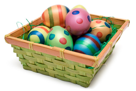 Colorful easter eggs in a wooden basket. Isolated on a white background. photo