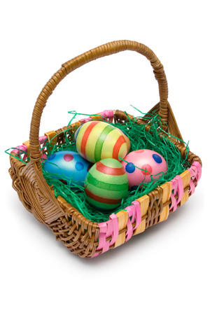 Wooden basket full of Easter eggs. Isolated on a white background. photo