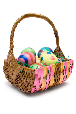 eastertime: Woven basket full of colorful eggs. Isolated on a white background.