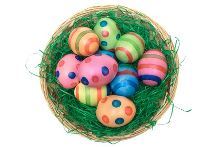 Easter eggs in a wooden basket. Isolated on a white background. photo