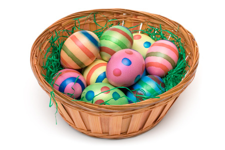 Colorful eggs on green grass in a wooden basket. Isolated on a white background. photo