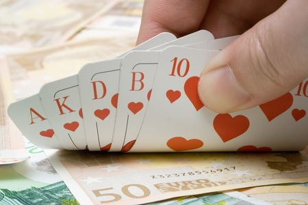 debt goals: Revealing a royal flush on a money background. Stock Photo
