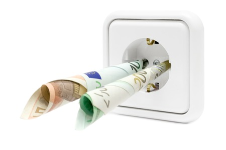 Banknotes attached to a power socket. Isolated on a white background. Stock Photo