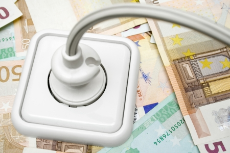 Plugged power cable isolated on a money background. Stock Photo