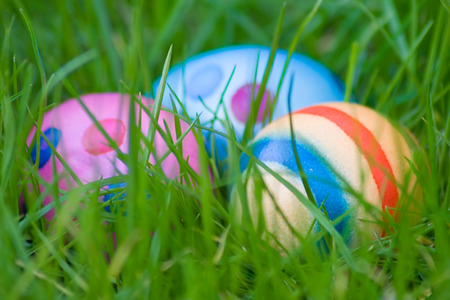 Three colorful eggs hidden in green grass. Shallow depth of field. photo