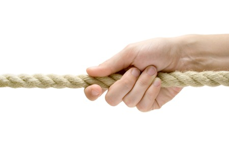 Female hand pulling a rope. Isolated on a white background. photo